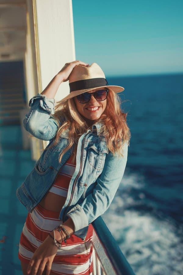 Lycklig handelsresandekvinna i toothy leende för hatt på kryssningskeppet royaltyfri fotografi