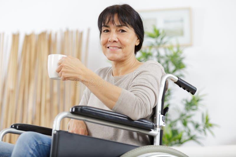 Lycklig handikappad hög kvinna som har koppkaffe arkivfoton