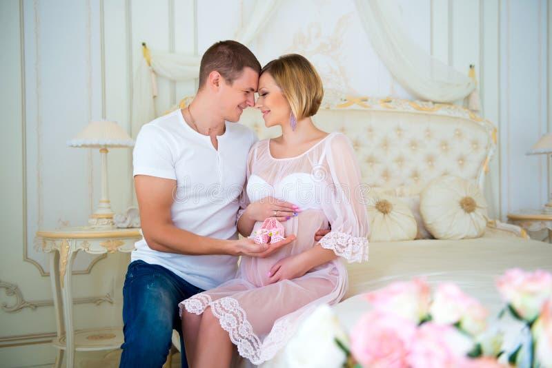 Lycklig havandeskap: makeinnehavet behandla som ett barn byten nära buken hans gravida fru arkivbilder