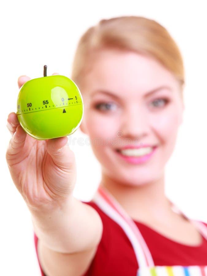 Lycklig hemmafru eller kock i tidmätare för äpple för kökförklädevisning royaltyfri fotografi