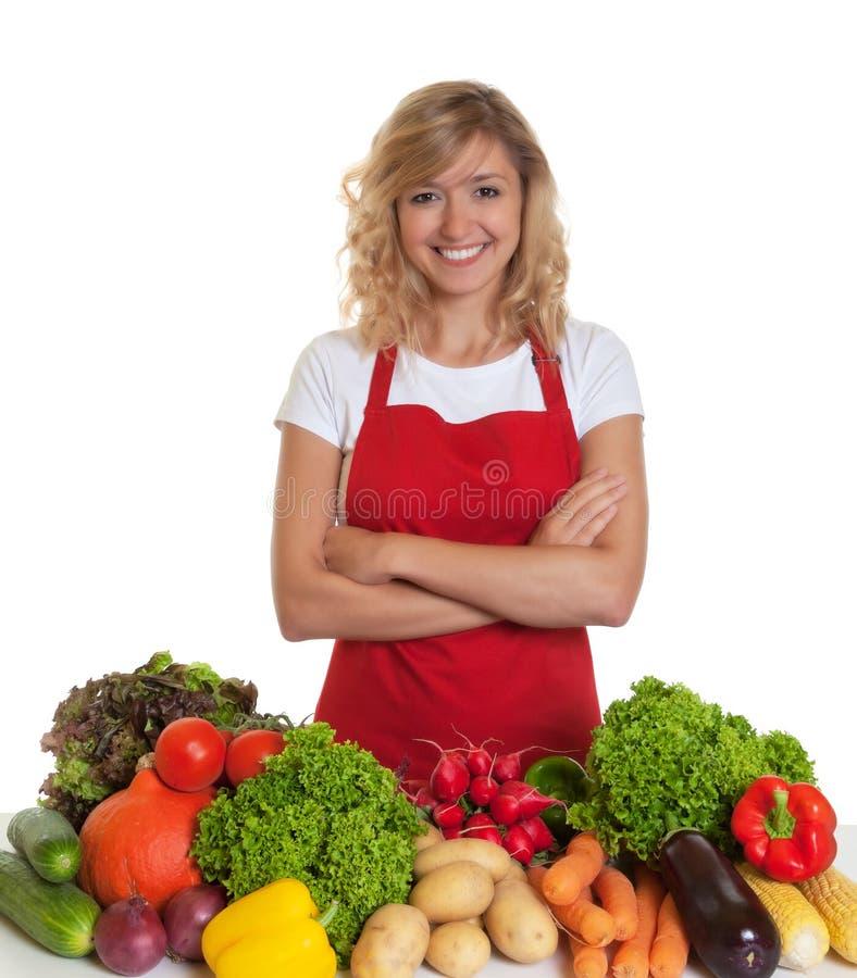 Lycklig hemmafru med det röda förklädet och nya grönsaker royaltyfria bilder