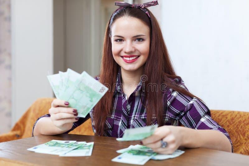 Lycklig hemmafru med många euro royaltyfria foton