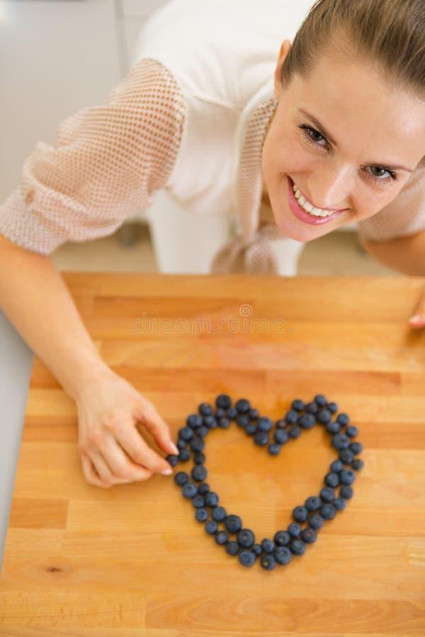 Lycklig hemmafrudanandehjärta med blåbär arkivfoto