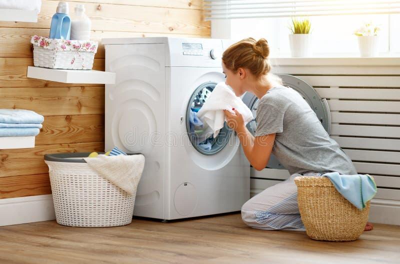 Lycklig hemmafrukvinna i tvättstuga med tvagningmaskinen arkivbilder