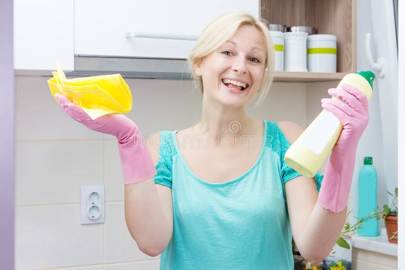 Lycklig hemmafrulokalvård i köket royaltyfri fotografi