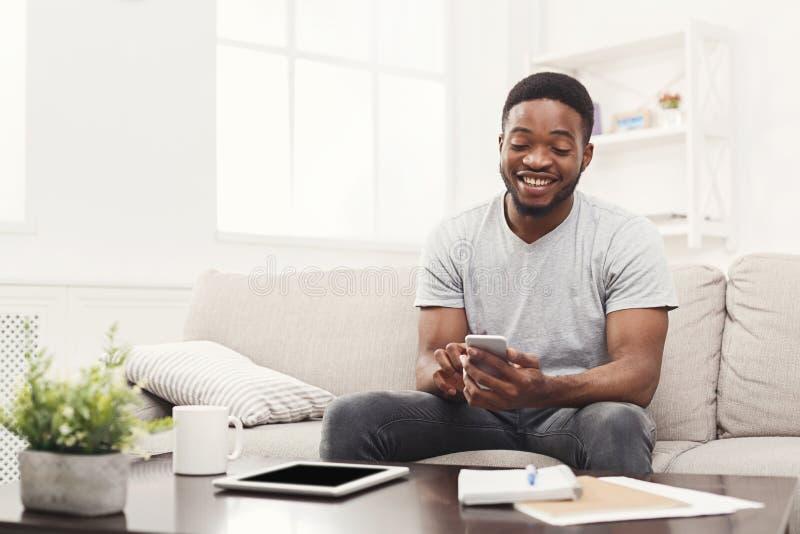 Lycklig hemmastadd messaging för ung man på mobil royaltyfria foton
