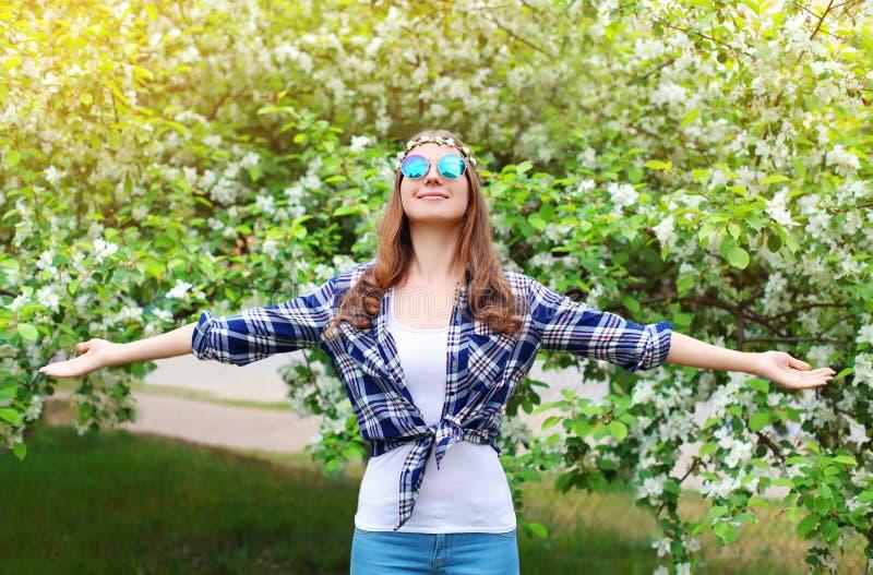 Lycklig hippiekvinna som tycker om i blomningvårträdgård royaltyfri foto