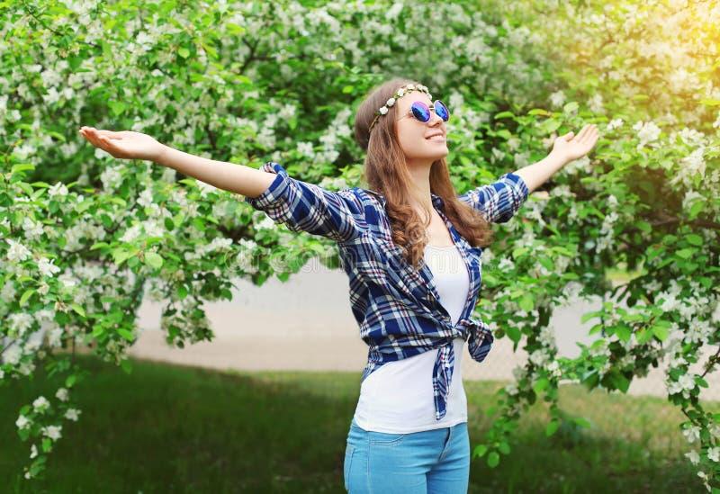 Lycklig hippiekvinna som tycker om lukten i blomningvårträdgård royaltyfri fotografi