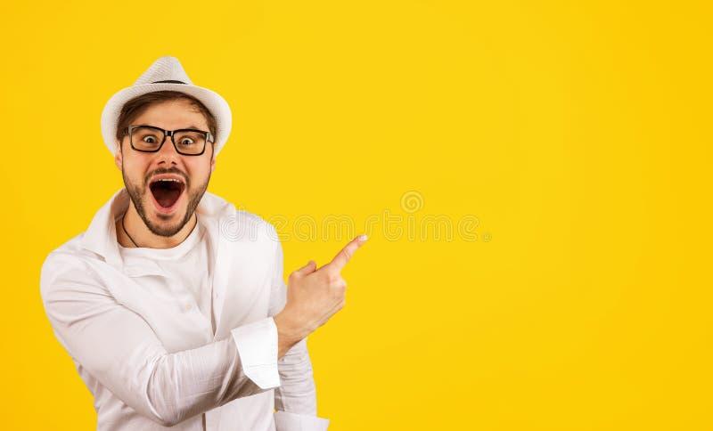 Lycklig hipster som pekar upp på guling fotografering för bildbyråer
