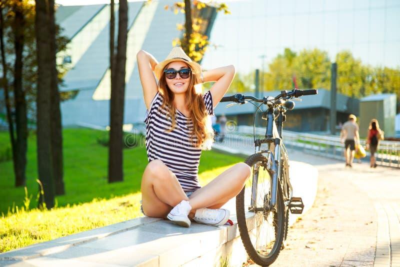 Lycklig Hipsterflicka med hennes cykel i staden royaltyfri bild