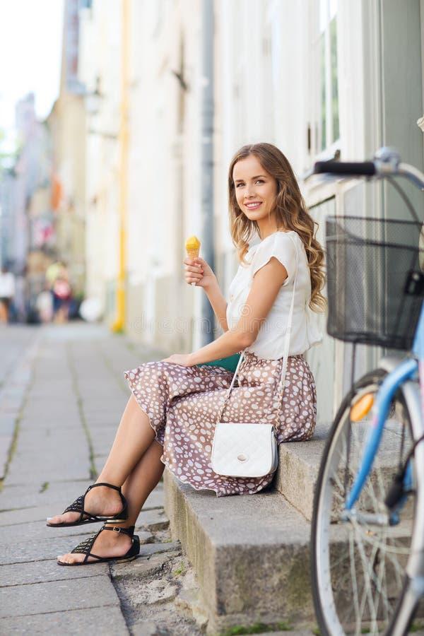 Lycklig hipsterkvinna med cykeln som äter glass arkivfoton