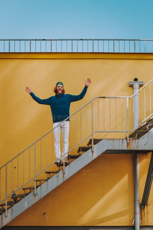 Lycklig hipsterman som rymmer h?nder upp p? trappa arkivbild