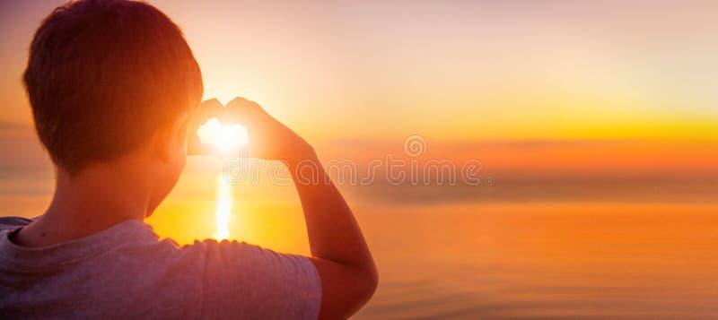 Lycklig hjärta för pysungedanande med hans händer över solnedgånghavet royaltyfri fotografi