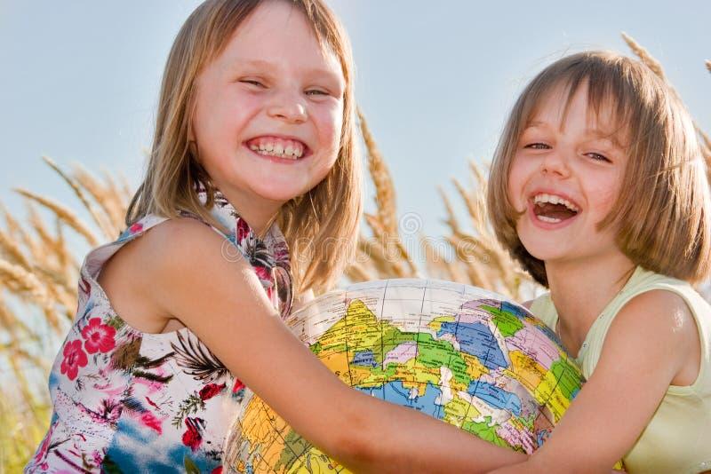 lycklig holding för flickajordklot fotografering för bildbyråer