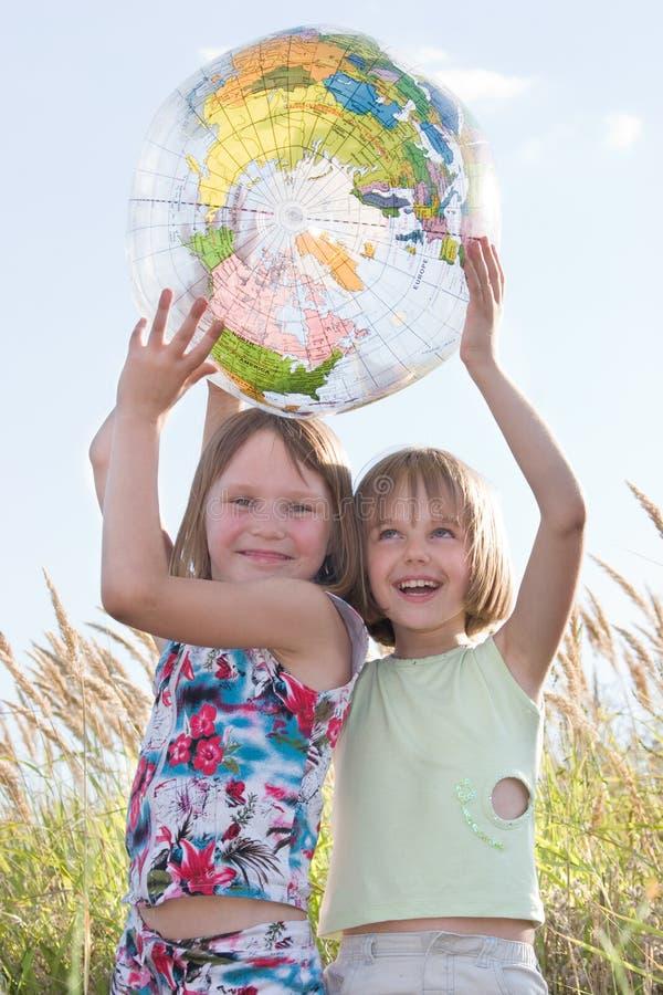 lycklig holding för flickajordklot arkivbilder