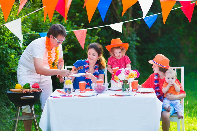 Lycklig holländsk familj som har gallerpartiet i trädgård royaltyfri fotografi