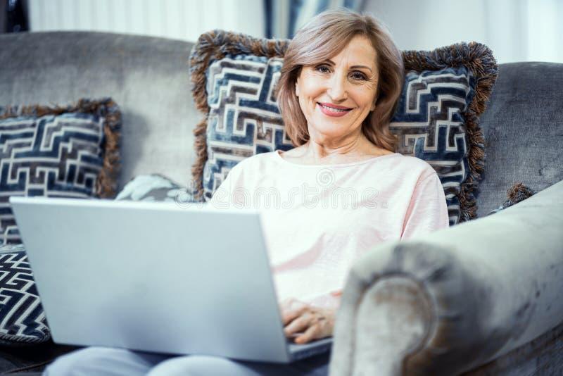 lycklig home bärbar dator genom att använda kvinnan arkivfoton