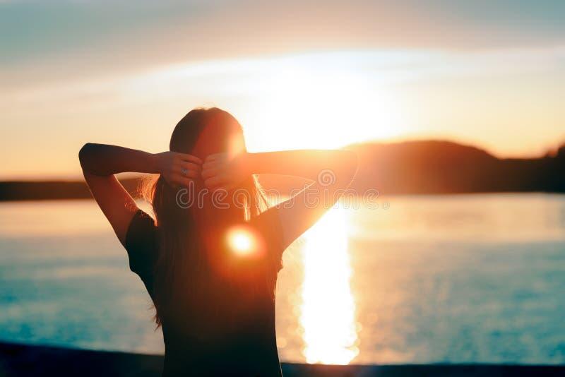 Lycklig hoppfull kvinna som ser solnedgången vid havet royaltyfria foton