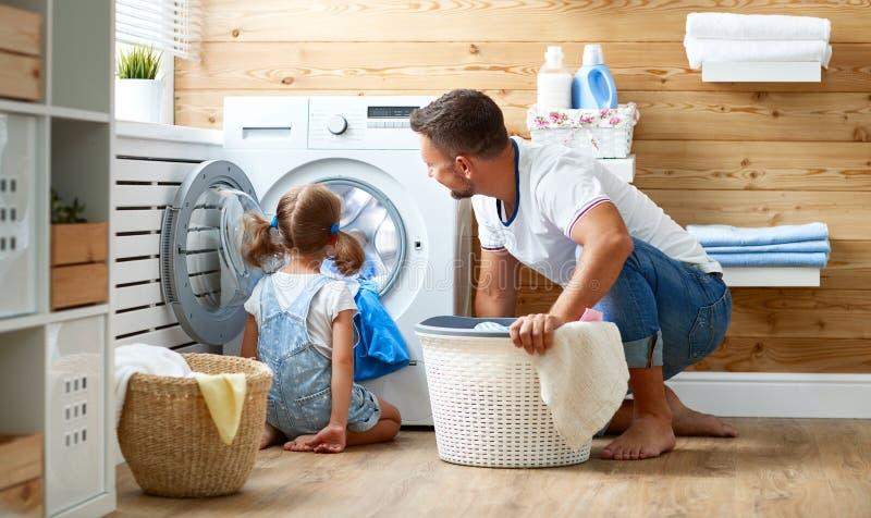 Lycklig husägare och barn för fader för familjman i tvätteri med arkivbild