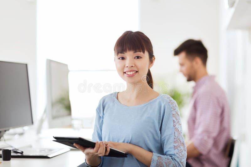 Lycklig idérik kvinnlig kontorsarbetare med minnestavlaPC royaltyfri bild