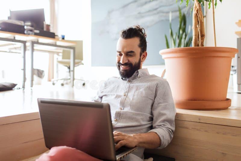 Lycklig idérik manlig kontorsarbetare med bärbara datorn arkivfoto