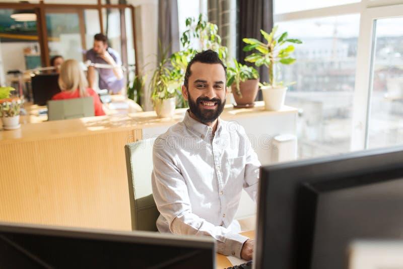 Lycklig idérik manlig kontorsarbetare med datoren arkivfoto