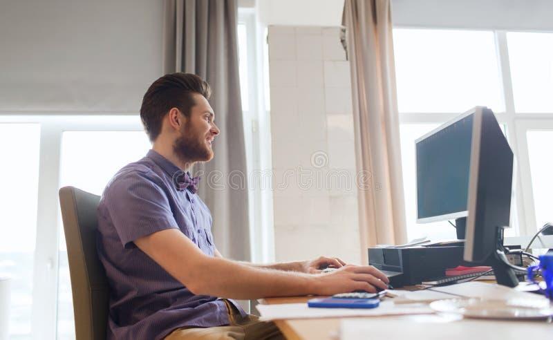 Lycklig idérik manlig kontorsarbetare med datoren royaltyfri bild