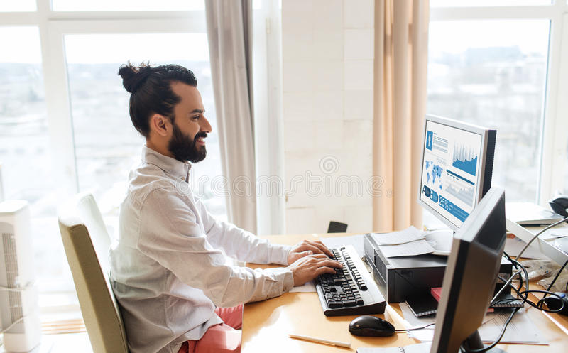 Lycklig idérik manlig kontorsarbetare med datoren royaltyfria foton