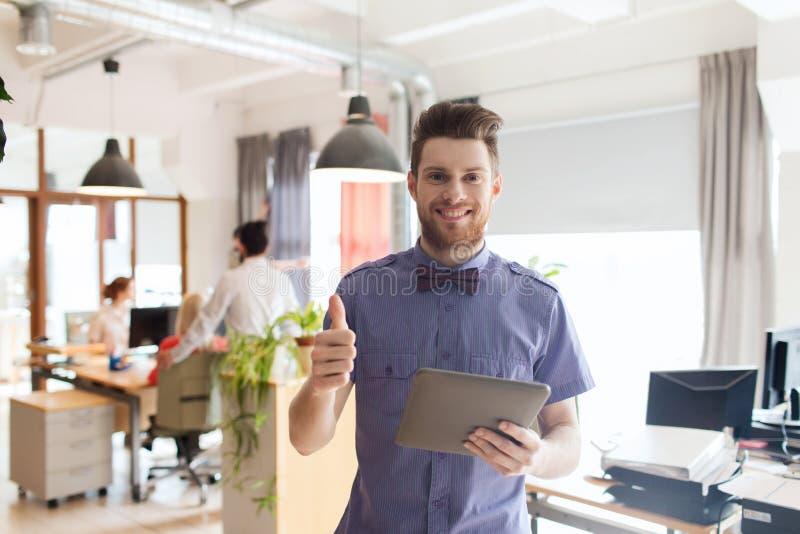 Lycklig idérik manlig kontorsarbetare med minnestavlaPC arkivfoton