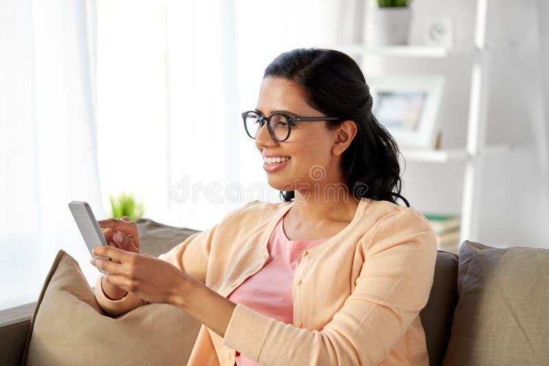 Lycklig indisk kvinna som hemma använder smartphonen fotografering för bildbyråer
