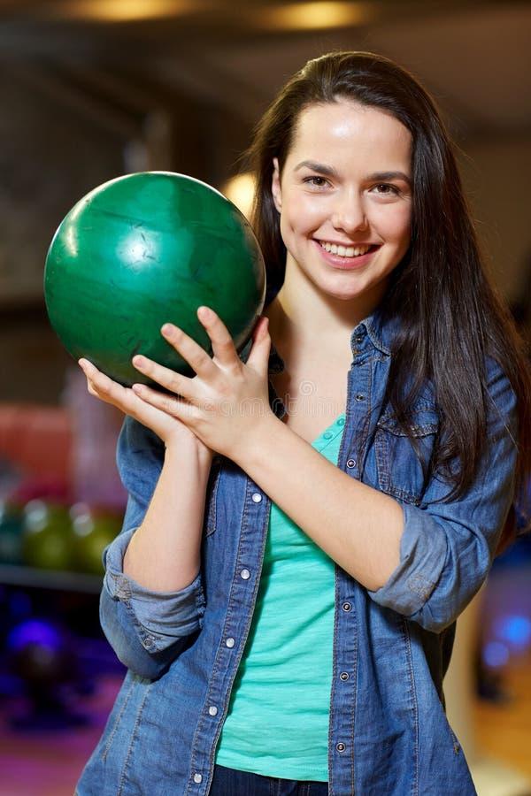Lycklig innehavboll för ung kvinna i bowlingklubba royaltyfri bild