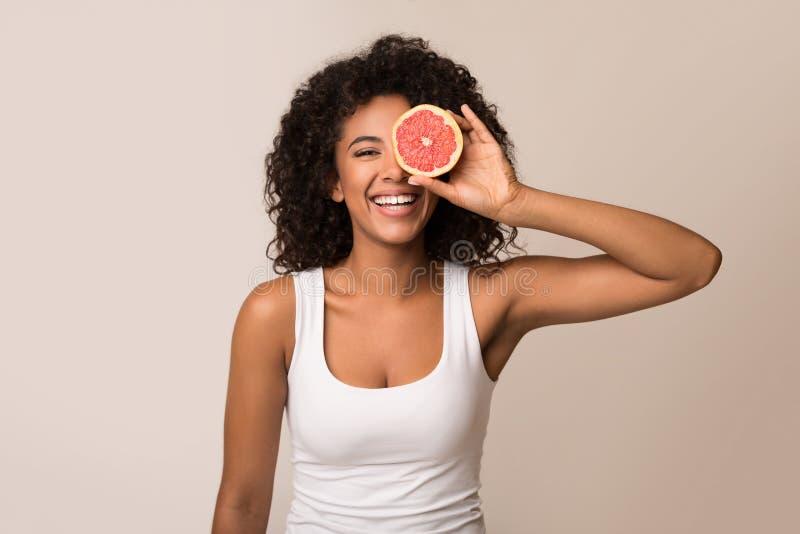 Lycklig innehavhalva för ung kvinna av grapefrukten royaltyfria bilder