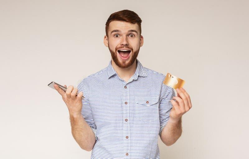 Lycklig innehavkreditkort och mobiltelefon för ung man arkivfoton