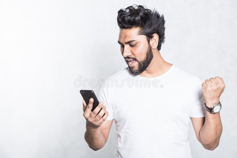 Lycklig innehavsmartphone f?r ung man och fira hans framg?ng arkivbilder