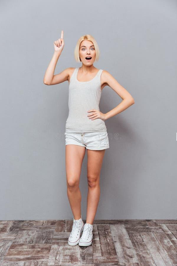 Lycklig inspirerad ung kvinna som pekar upp och har en idé royaltyfri fotografi