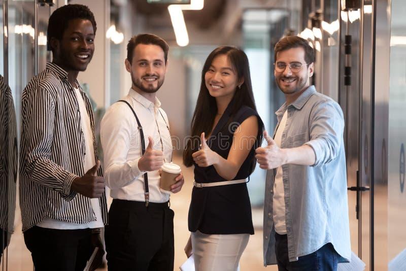 Lycklig internationell grupp för affärsfolk som visar upp tummar, stående royaltyfria foton