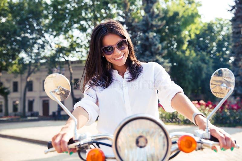 Lycklig italiensk kvinna som rider en sparkcykel arkivfoto