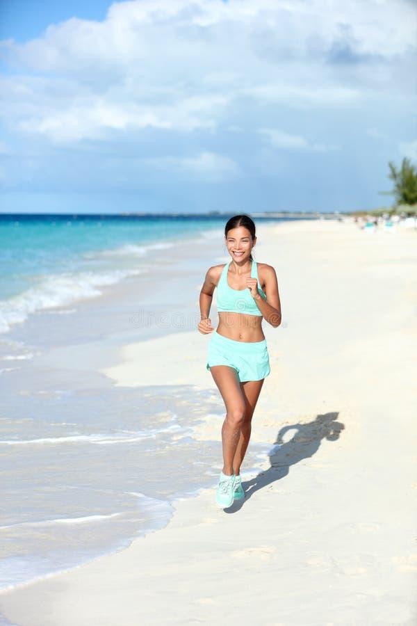 Lycklig jogga kvinnaspring på den soliga stranden som bor ett passformliv fotografering för bildbyråer