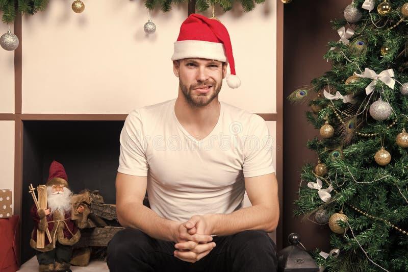 Lycklig jultomtenman mannen i den santa hatten v?ntar p? julg?va Leveransjulg?vor Morgonen f?r Xmas Direktanslutet royaltyfri bild