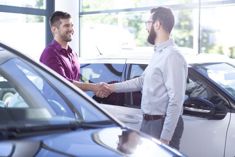 Lycklig köpare av den nya bilen som skakar händer med återförsäljaren efter transaktion i salongen royaltyfria foton
