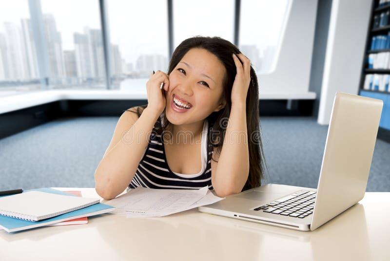 Lycklig kinesisk asiatisk kvinna som arbetar och studerar på hennes sammanträde för bärbar datordator på det moderna kontoret arkivfoto