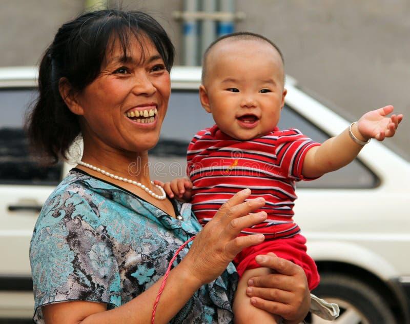 Lycklig kinesisk kvinna med en behandla som ett barn i henne armar royaltyfri bild