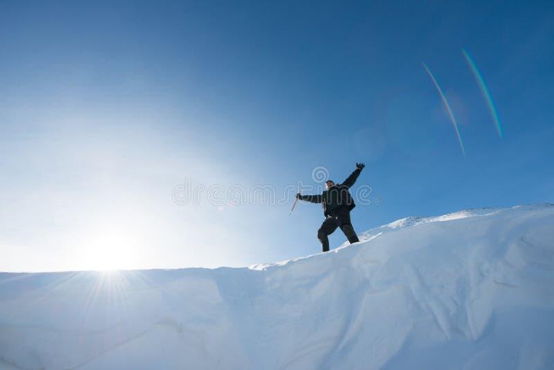 Lycklig klättrare med en isyxa i de snöig bergen fotografering för bildbyråer