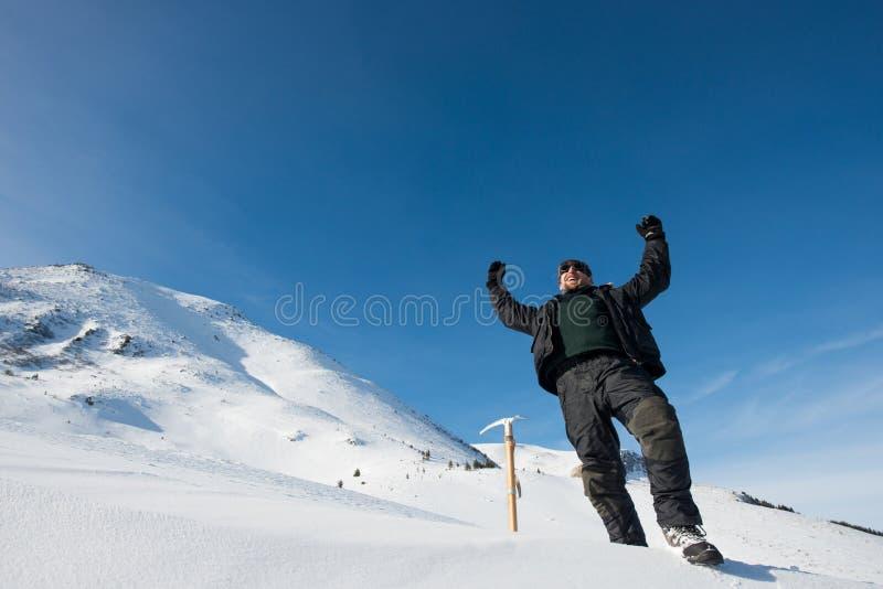 Lycklig klättrare med en isyxa i de snöig bergen royaltyfri foto