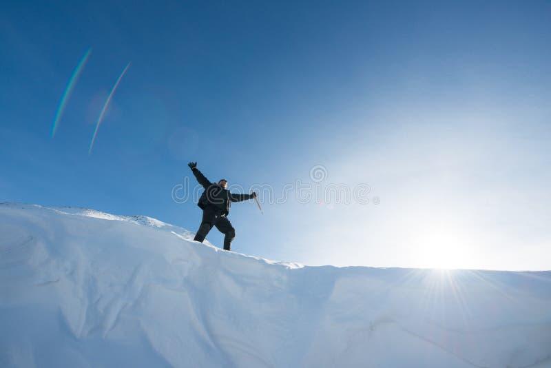 Lycklig klättrare med en isyxa i de snöig bergen royaltyfria bilder