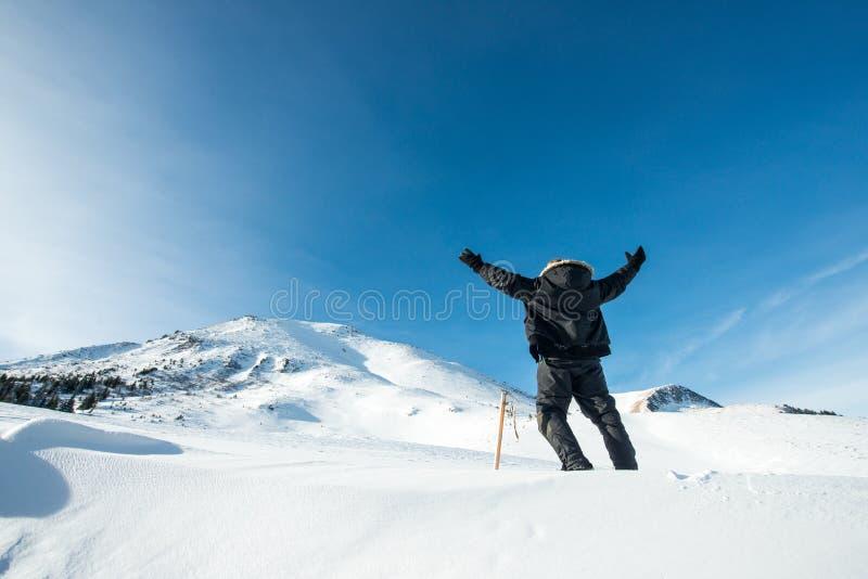 Lycklig klättrare med en isyxa i de snöig bergen arkivfoto