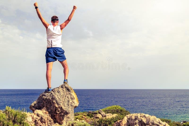 Lycklig klättrarelöpare som når mannen för livmålframgång royaltyfria foton