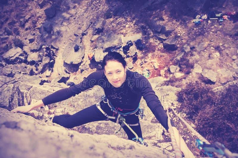 Lycklig klättringvägg för ung kvinna royaltyfri foto
