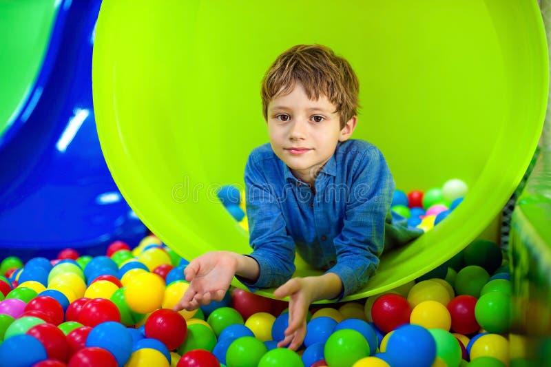Lycklig knatte som ligger på färgrika bollar och ser kameran med leende royaltyfri foto