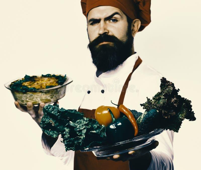 Lycklig kock som framlägger sallad av grönsaker arkivbilder